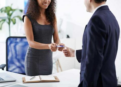 Woman handing her business card to man